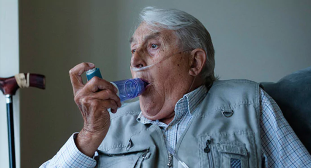 Older man inhaling breathing test